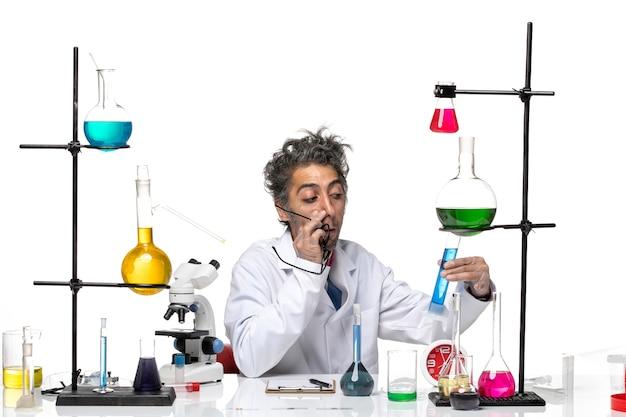 Vue de face scientifique masculin en costume médical blanc travaillant avec des solutions