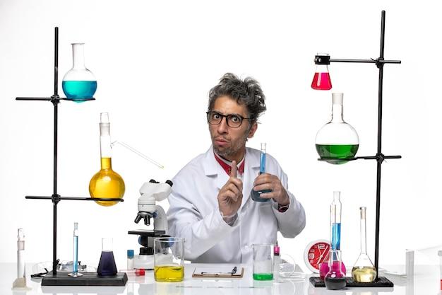 Vue de face scientifique masculin en costume médical tenant une solution bleue sur blanc bureau laboratoire coronavirus santé covid