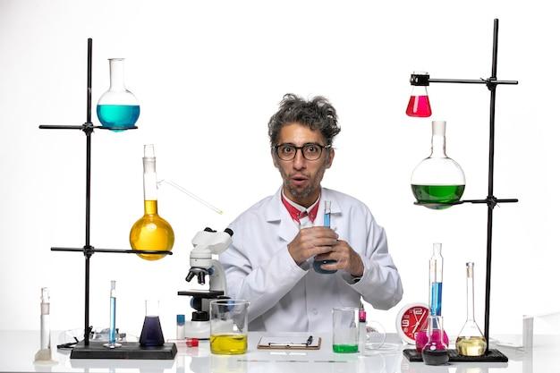 Vue de face scientifique masculin en costume médical tenant une solution bleue sur fond blanc clair laboratoire coronavirus santé covid