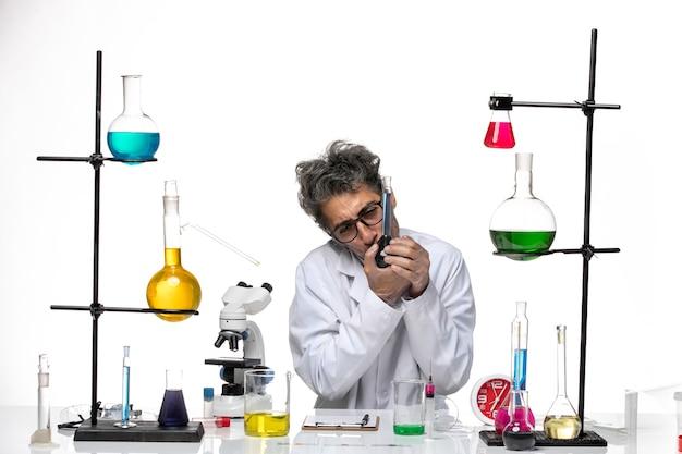 Vue de face scientifique masculin en costume médical tenant une solution bleue sur fond blanc laboratoire coronavirus santé covid