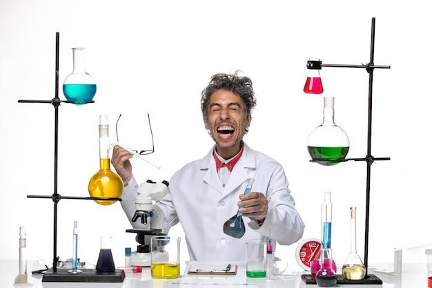 Vue de face scientifique masculin en costume médical tenant une solution bleue et se réjouissant sur fond blanc virus de laboratoire coronavirus santé covid