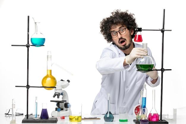 Vue de face scientifique masculin en costume médical tenant des solutions sur un espace blanc