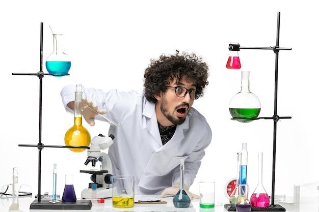 Vue de face scientifique masculin en costume médical travaillant avec des solutions sur un bureau blanc