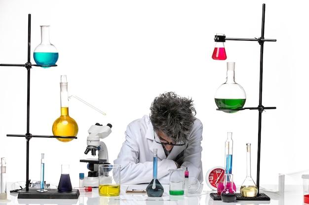 Vue de face scientifique masculin en costume médical travaillant avec des solutions