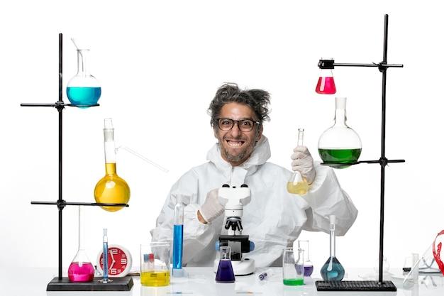 Vue de face scientifique masculin fou en combinaison de protection spéciale assis autour de la table avec des solutions sur fond blanc virus de la science du laboratoire covid