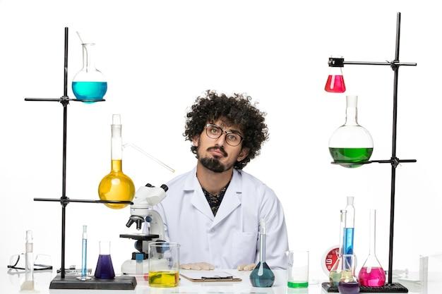 Vue de face scientifique masculin fou en costume médical assis sur un espace blanc