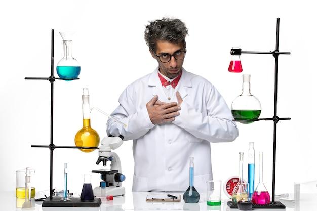 Vue de face scientifique masculin posant avec des solutions