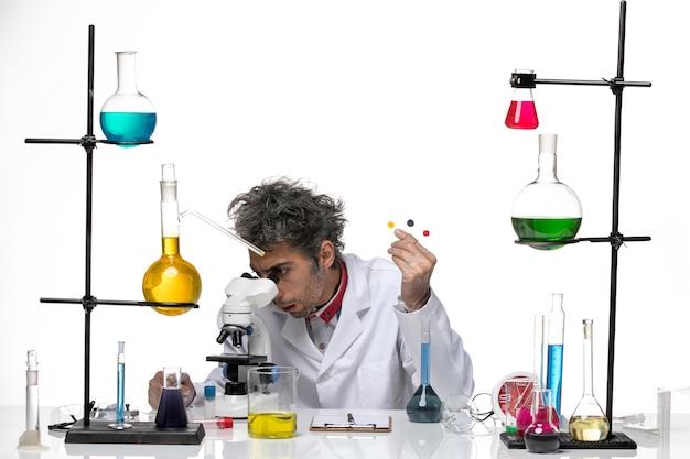 Vue de face scientifique masculin tenant des échantillons et à l'aide d'un microscope sur fond blanc laboratoire de santé coronavirus covid