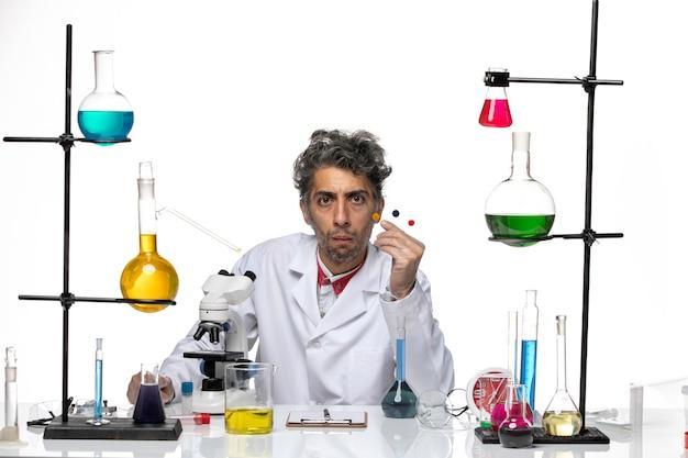 Vue de face scientifique masculin tenant des échantillons sur fond blanc covid laboratoire de santé coronavirus