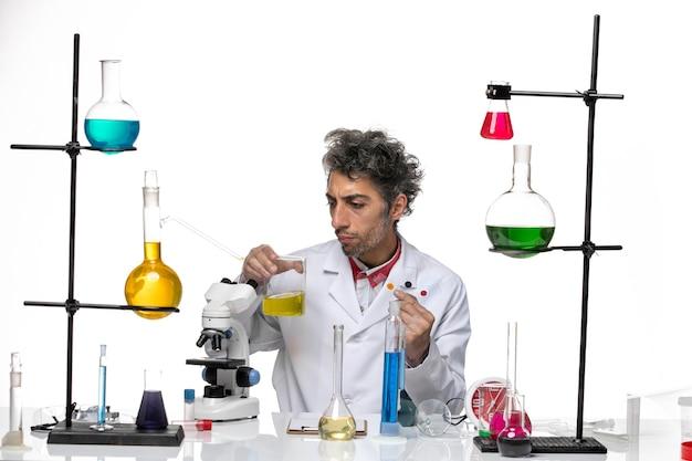 Vue de face scientifique masculin tenant des échantillons et une solution sur fond blanc laboratoire de santé coronavirus covid