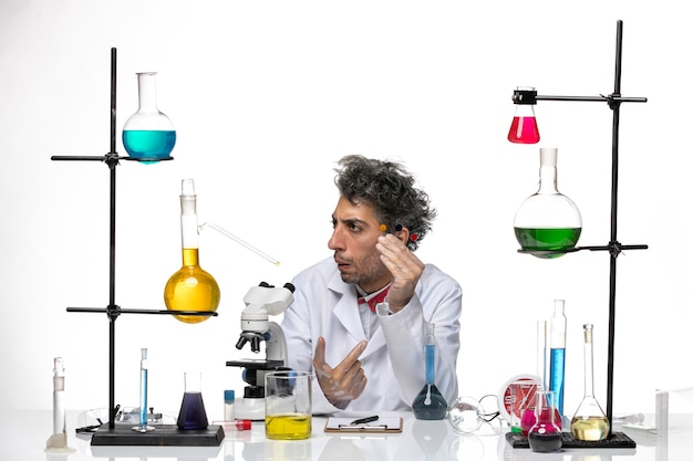 Vue de face scientifique masculin tenant quelque chose sur fond blanc laboratoire de santé coronavirus covid