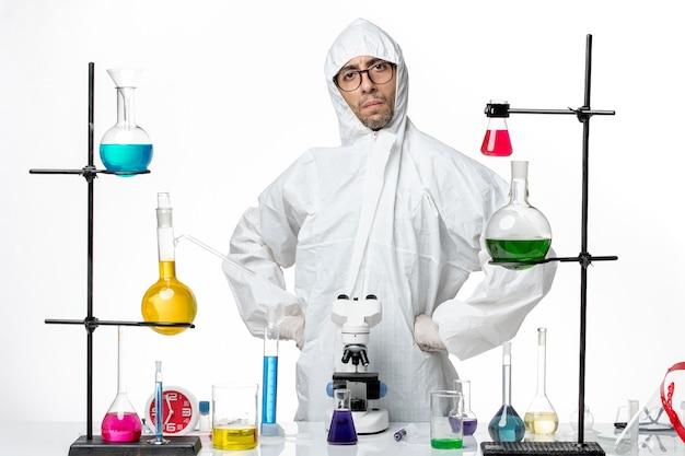 Vue de face scientifique masculin en tenue de protection spéciale debout autour de la table avec des solutions