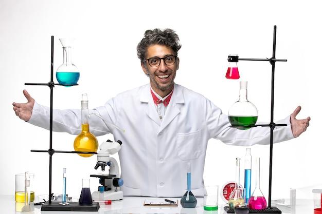 Vue de face scientifique masculin travaillant avec des solutions et souriant