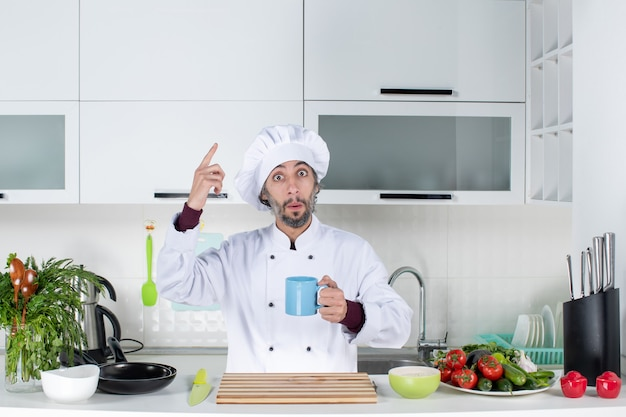 Vue de face se demandait chef masculin en chapeau de cuisinier tenant une tasse debout derrière la table de la cuisine