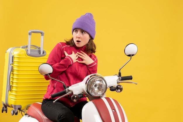 Vue de face se demandait jeune femme sur un cyclomoteur en regardant quelque chose