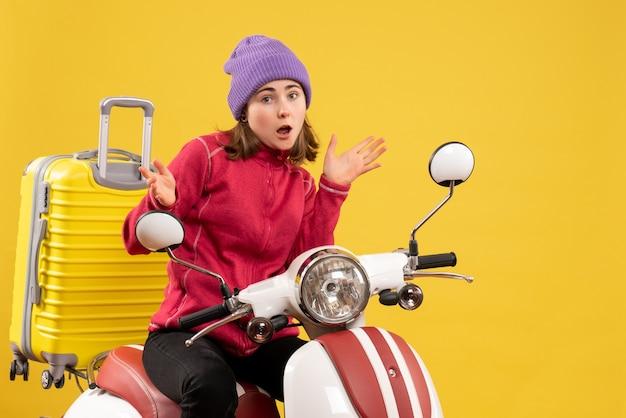 Vue de face se demandait jeune fille au chapeau violet sur cyclomoteur