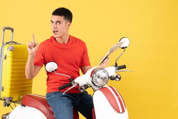 Vue de face se demandait jeune homme sur une carte de tenue de cyclomoteur surprenant avec une idée