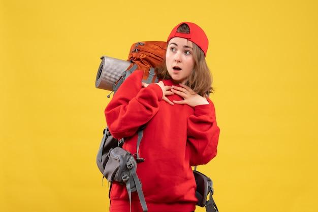 Vue de face se demandait jeune touriste avec sac à dos et bonnet rouge mettant les mains sur sa poitrine