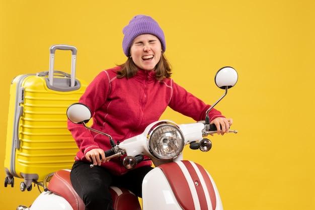 Vue de face se réjouit de la jeune fille sur un cyclomoteur se sentant prête à bouger