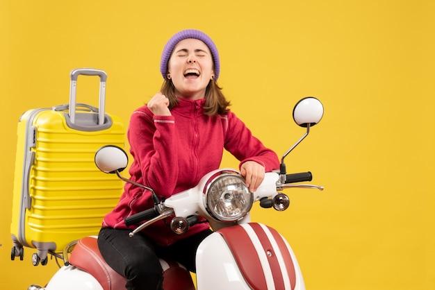 Vue de face se réjouit de la jeune fille sur cyclomoteur