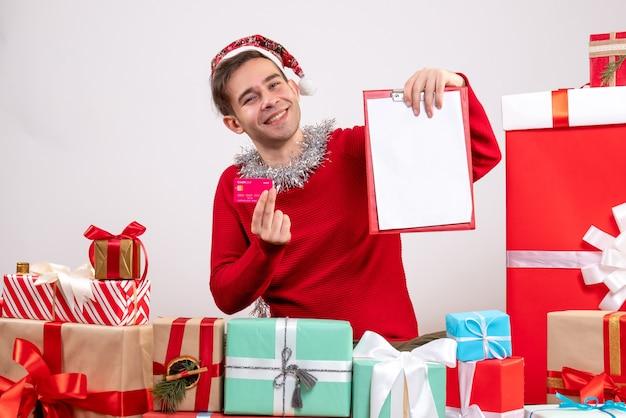 Vue de face se réjouit jeune homme tenant le presse-papiers et la carte assis autour de cadeaux de noël