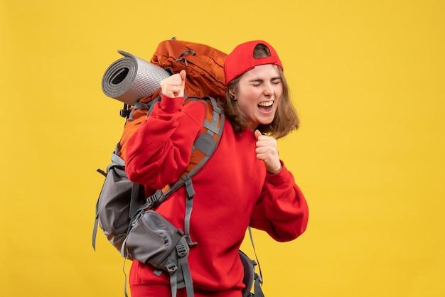 Vue de face se réjouit jeune touriste avec sac à dos et bonnet rouge