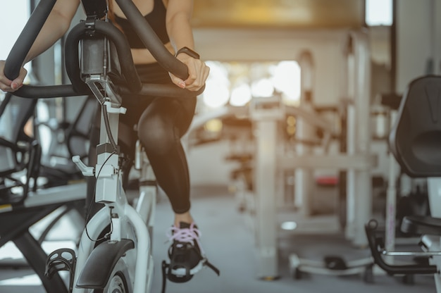 Vue de face d'une séance d'entraînement de femme avec un vélo les femmes font de l'exercice dans la salle de sport pour un mode de vie sain
