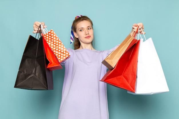 Une vue de face séduisante femme en robe-chemise bleue tenant des paquets d'achat sur bleu