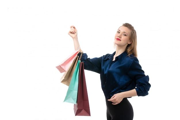 Une vue de face séduisante jeune femme en blouse bleue pantalon noir posant holding shopping packages sur le fond blanc de la mode des vêtements élégants