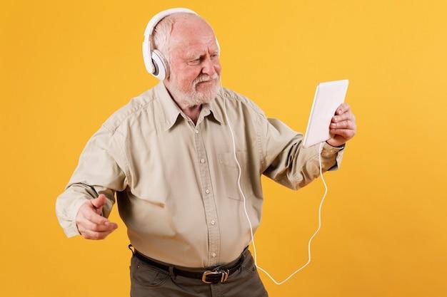 Vue de face senior écoute de la musique sur tablette