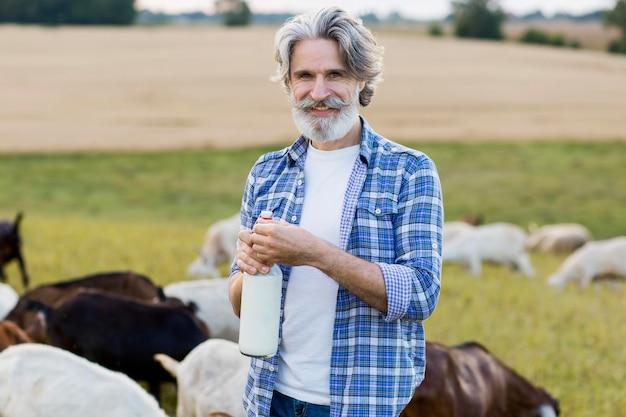 Vue de face senior holding bouteille de lait de chèvre