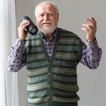 Vue de face senior jouant des chansons sur le haut-parleur