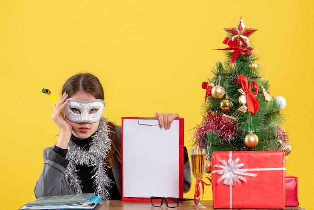 Vue de face sérieuse jeune fille avec masque assis à la table tenant arbre de noël bruiteur et cocktails cadeaux