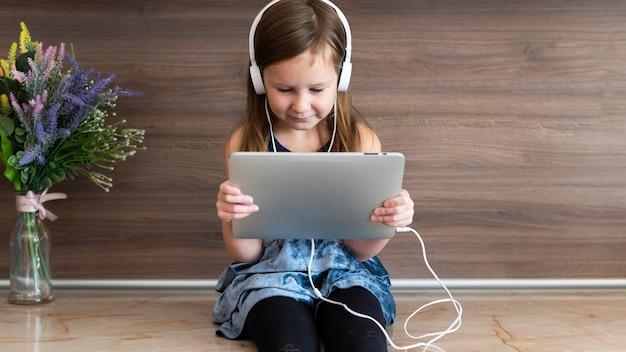 Vue de face de smiley girl à l'aide de tablette avec un casque