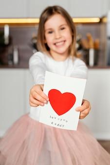 Vue de face de smiley girl tenant une carte pour la fête des pères