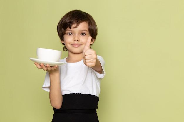 Une vue de face smiling cute boy holding white tasse de café en t-shirt blanc sur le bureau de couleur pierre