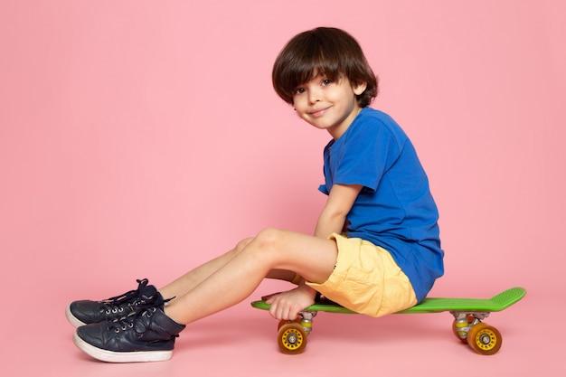 Une vue de face smiling cute boy in blue t-shirt riding skateboard sur le plancher rose