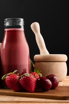 Vue de face smoothie en bouteille avec des fraises et des cerises