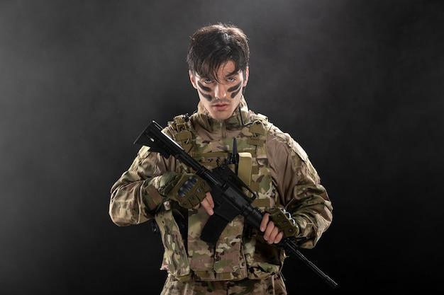 Vue de face d'un soldat masculin combattant pendant l'opération avec un fusil sur un mur sombre