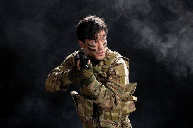 Vue de face d'un soldat masculin combattant en tenue de camouflage avec un fusil sur un mur noir