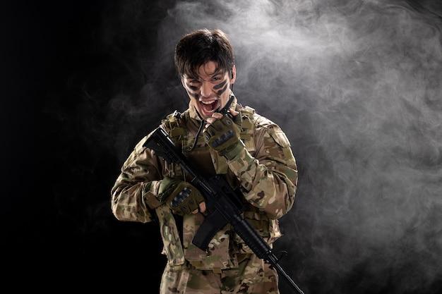 Vue de face d'un soldat masculin avec un fusil à l'aide d'un mur noir de talkie-walkie