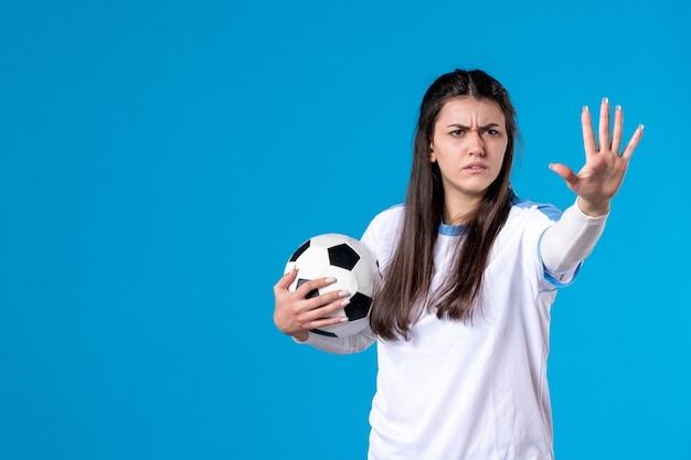 Vue de face a souligné jeune femme avec ballon de foot