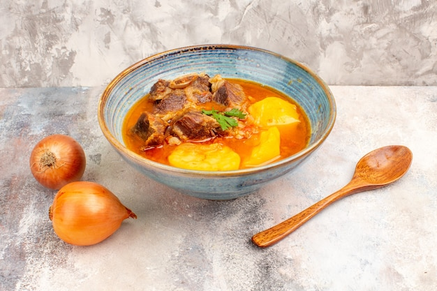 Vue de face de la soupe bozbash une cuillère en bois d'oignons sur fond nu