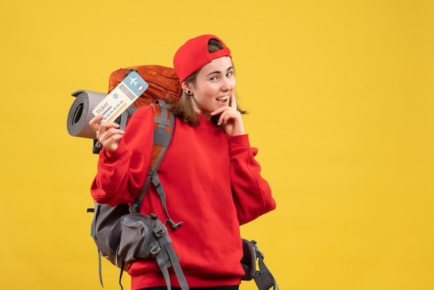 Vue de face souriant campeur féminin avec sac à dos tenant un billet de voyage
