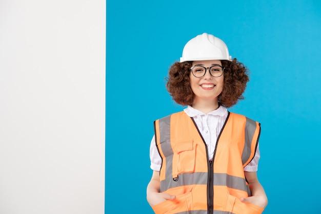 Vue de face souriant constructeur féminin en uniforme sur bleu