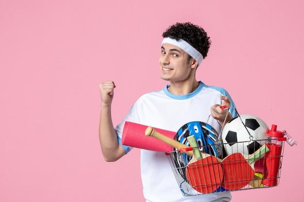 Vue de face souriant jeune homme en vêtements de sport avec panier plein de choses sportives
