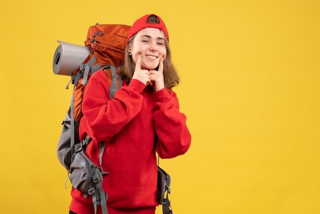 Vue de face souriant jeune touriste avec sac à dos et bonnet rouge mettant le doigt sur sa joue