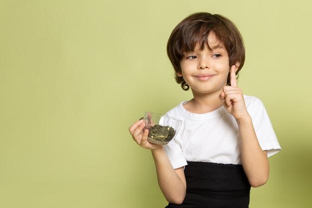Une vue de face souriant mignon garçon en t-shirt blanc tenant des espèces sur le sol de couleur pierre
