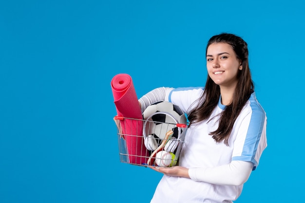 Vue de face souriante jeune femme avec panier après le sport shopping