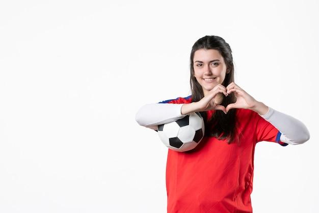 Vue de face souriante jeune femme en vêtements de sport avec ballon de foot